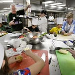 Youngsters cook in the Kellogg Center kitchens with their grandparents during Grandparents University at MSU Tuesday , 2015.