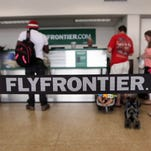 Passengers check in at Frontier Airlines for an afternoon flight at the New Castle County Airport on Aug. 9, 2013.