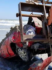 A forklift is used to remove a red Honda Prelude from the beach in Port Aransas. The vehicle was left on the beach before Hurricane Harvey made landfall in the city.