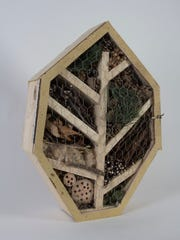 Students in the 3-D Concepts class at University of Wisconsin-Milwaukee made insect hotels from discarded wood to provide habitat for the decreasing population of bugs. Nicole Lorscheter created this hotel in the shape of a leaf is filled with leaves, sticks and pine cones.