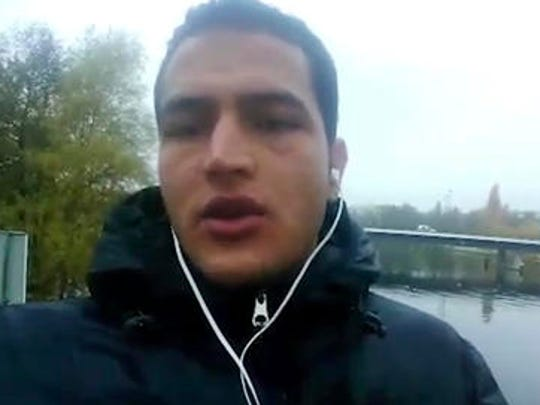"This image made from video released by Amaq News Agency of the Islamic State group on Friday, Dec. 23, 2016 shows Anis Amri, a Tunisian suspect in the Berlin truck attack pledging allegiance to its leader Abu Bakr al-Baghdadi and vowing to fight against what he calls ""the Crusader pigs."" The video, which appeared to have been taken by Anis Amri himself, shows him standing on a footbridge in the north of Berlin, not far from where he allegedly hijacked the truck used in the attack that killed 12 people and injured dozens more at a Christmas market on Monday."