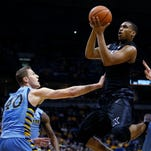 Xavier's Trevon Bluiett is fouled as he shoots against Marquette's Luke Fischer (40) and Henry Ellenson (13) during the second half of an NCAA college basketball game Saturday in Milwaukee.