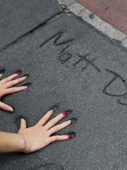In this May 9, 2017 file photo, a tourist places her hands on the handprints of actor Matt Damon in the forecourt of the TCL Chinese Theatre in the Hollywood section of Los Angeles. The storied Hollywood Boulevard movie palace opened its doors on May 18, 1927. (AP Photo/Jae C. Hong)