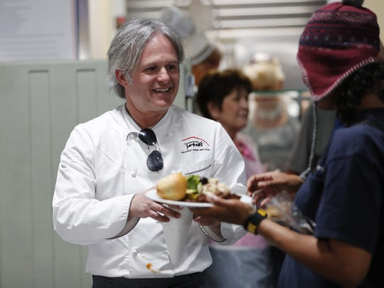 Chef Mark Tarbell serves after preparing meals for the homeless at St. Vincent de Paul in Phoenix on March 6, 2018.