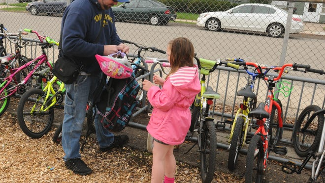 Scott Knuth and Kindergartner Paige Knuth put away their bikes during the Smith Elementary school National Bike to School Day where Oshkosh North, Oshkosh West and the Timber Rattler mascots showed support along with the Oshkosh North baseball team as they did activities before school wi the students.
