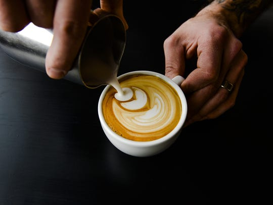 Jonathan Jarrow of Harbinger Coffee pours a latte Wednesday,