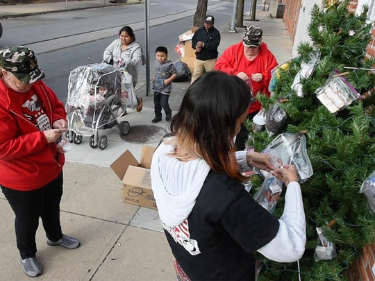 Local Feed the Vets of York County volunteers add items to the Blessing Tree for the Homeless in front of Coffee, Teas, & Thee at 15 South Pershing in York Monday November 28, 2016.