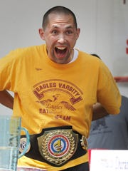 Dan Cadirao of Irondequoit puts on the winner's belt after triumphing at the hot dog-eating contest in Irondequoit on July 4, 2015.