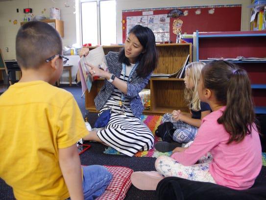 Jing Xia reads to students in her kindergarten class,