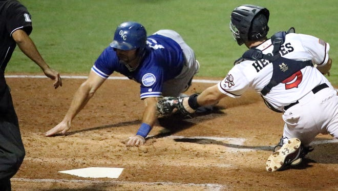 El Paso Chihuahuas catcher Austin Hedges reaches for the tag on OKC base runner Brandon Hicks as Hicks reaches for home plate Wednesday night at Southwest University Park. Hicks protested after the umpire ruled him out.