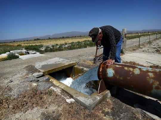 Lifelong rancher and farmer Tom Moura takes a drink of well water flowing on his ranch north of Lovelock on Aug. 9, 2015.