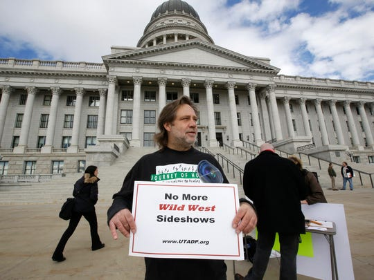 In this Jan. 27, 2015, file photo, Randy Gardner of Salt Lake City, the older brother of Ronnie Lee Gardner, the last inmate to be killed by firing squad in Utah in 2010, protests with a group opposed to capital punishment plans over one lawmaker's plan to resurrect the use of firing squads, outside the Utah State Capitol, in Salt Lake City.