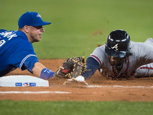 Toronto Blue Jays' Justin Smoak, left, tags out Atlanta Braves' Cameron Maybin to complete an unassisted double play during seventh inning interleague baseball action in Toronto on Sunday, April 19, 2015. (Darren Calabrese/The Canadian Press via AP)   MANDATORY CREDIT