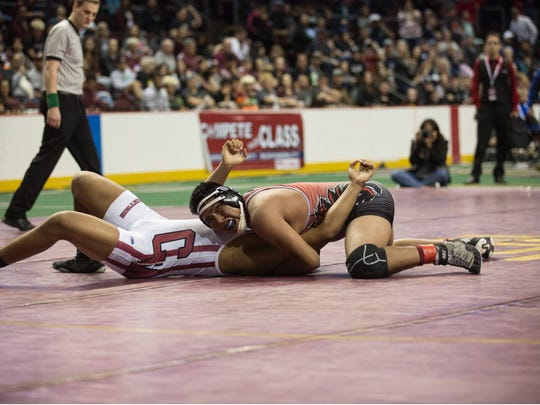 Shiprock's Logan Charley, top, pins Robertson's Darian Duran to win the A/4A 195-pound title on Saturday at the Santa Ana Star Center in Rio Rancho.