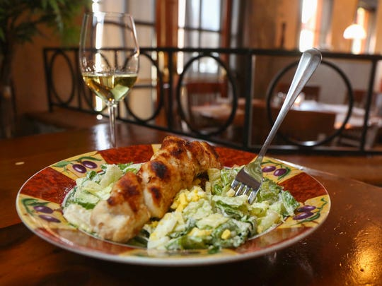 Chicken spiedini with a glass of white wine at Tursi's