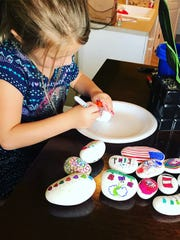 Erin Randall's daughter, Mya, paints rocks to hide