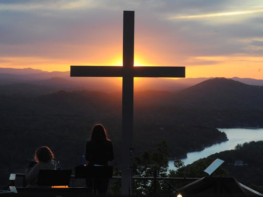 Musicians Amy Wilkie, left, and Mandy Keel of Bat Cave Baptist Church watch the sunrise as they perform during the 2012 Easter Sunrise Service at Chimney Rock State Park.