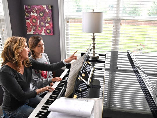 Laura Troup helps her daughter Avery with her piano lessons.She's a mother of three who is extremely passionate about AGAPE Nashville, an organization that, among other things, trains people to be foster parents and then works with DCS to place foster kids with families.Friday May 5, 2017, in Brentwood, TN