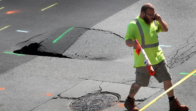 Workers continue to survey the scene of the sinkhole in the middle of the intersection of Ohio and Pennsylvania Streets Thursday,  July 5, 2018.