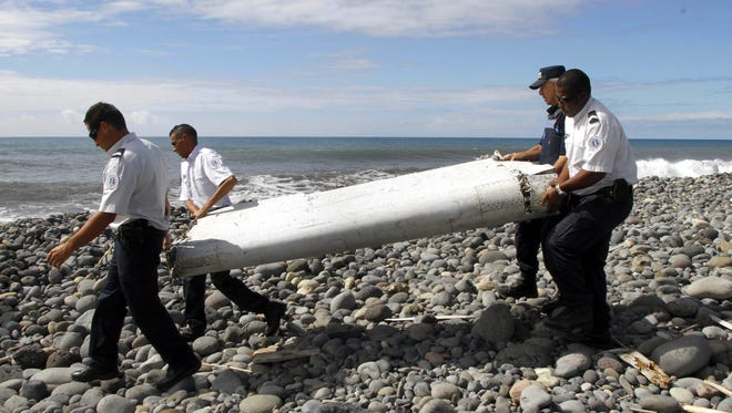 Officers carry a piece of debris from an unidentified aircraft apparently washed ashore in Saint-Andre de la Reunion, eastern La Reunion island, France.  A Malaysian government team is being dispatched to the French island of Reunion in the Indian Ocean, where newly found aircraft wreckage awakened speculation over flight MH370, which went missing last year with 239 people aboard.
