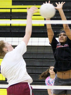 Shelbie Huffmon, left, spikes a ball towards Allyssa Madden during practice Thursday evening at the Tiger Pit.