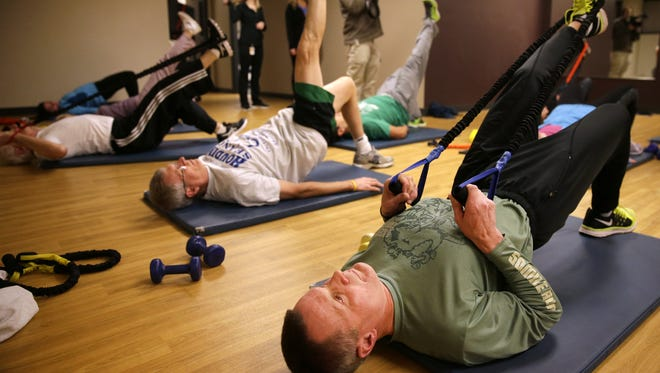 Jeff Curtin does a modified bridge earlier this month during the Weight of the Fox Valley's Wake Up for Wellness event at a Kimberly Clark fitness center in Neenah, Community business leaders were invited to the event to draw attention to the need for more corporate wellness programs.