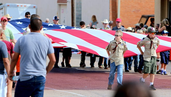Members of Boy Scouts of America Troop 91 of Henrietta carry a large American flag down South Main Street in Henrietta as part of the 86th annual Clay County Pioneer Reunion parade Saturday morning.