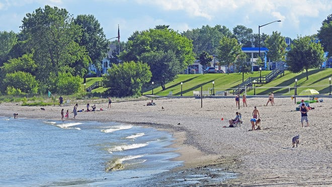 People enjoying Crescent Beach in Algoma.