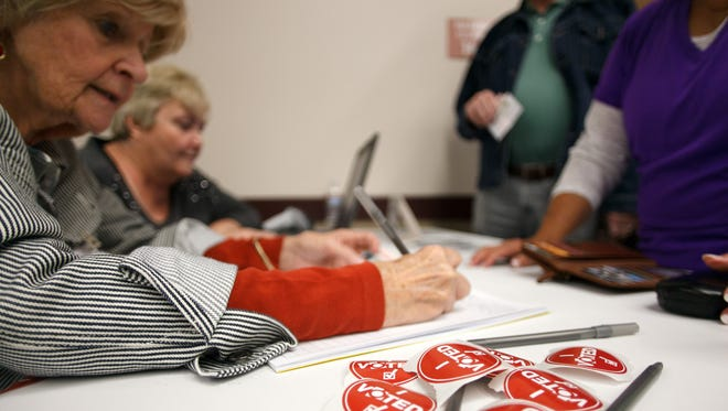 """""""I voted"""" stickers wait for voters to finish casting their ballots as they show their identification to poll workers at the Dixie Center in St. George Tuesday, Nov. 4, 2014."""