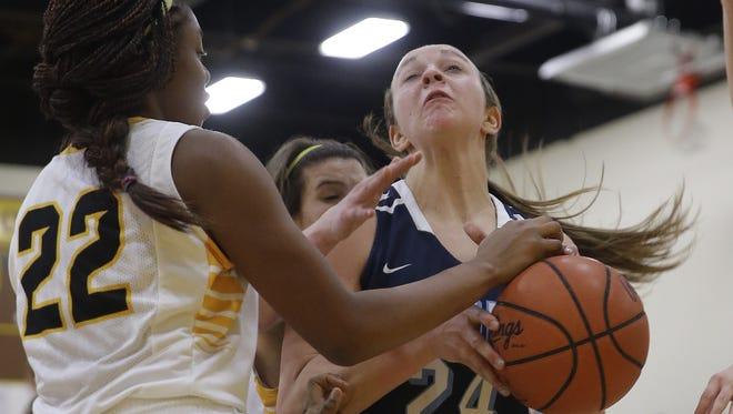 Mount Notre Dame's  Abbie Scholz (24) battles McAuley's Ariel Johnson (22) for a rebound during their basketball game, Thursday, Jan. 29, 2015.