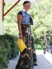 Lauren Simmonds wears a camouflage wrap skirt by HIS Inspiration Wrap Skirts; denim vest by Zara; black cotton cropped wrap shirt by Garage; and black leather wedge ankle boots from Fenty Puma by Rihanna.