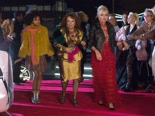 """In """"Absolutely Fabulous: The Movie,"""" Edina (Jennifer Saunders, center) and Patsy (Joanna Lumley) walk the red carpet with Edina's granddaughter (Indeyarna Donaldson Holness) in tow."""