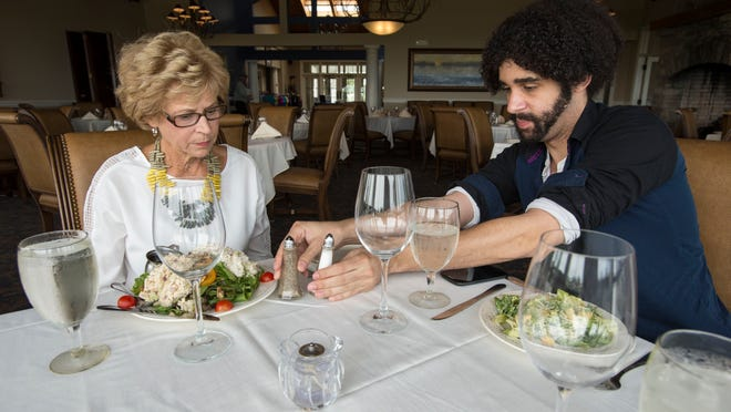 Grace Foxwell Murdoch and reporter Phil Davis enjoy lunch and discuss dining etiquette at Lighthouse Sound. Manners dictate that the salt and pepper are always passed together, and items are passed to the right. Food should be tasted before adding salt or pepper, as a courtesy to the cook.