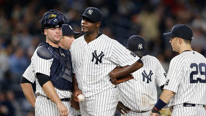 New York Yankees catcher Brian McCann watches as starting pitcher Michael Pineda (35) reacts on the mound after loading the bases during the sixth inning of a baseball game at Yankee Stadium in New York, Wednesday, May 11, 2016. Joining Pineda on the mound are Yankees shortstop Did Gregarious, second from right, and Yankees first baseman Dustin Ackley (29).