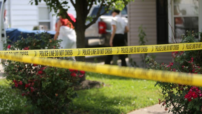 Police tape in front of a home on Hilda Avenue in Hamilton where police say Alfred Rutherford shot and killed his daughter, Lacey, and another male on Wednesday, June 18, 2014.
