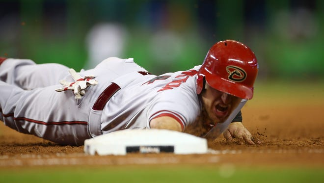 Arizona Diamondbacks' Cliff Pennington dives back on a pick off attempt by Miami Marlins' Brad Penny during the second inning of a baseball game in Miami, Thursday, Aug. 14, 2014.
