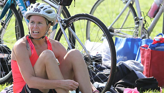 Christine Vetter of Plymouth changes her shoes before heading out on the running portion of the Winnebago County Triathlon on Sunday at Lake Winneconne Park.