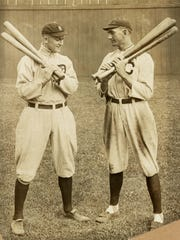 "Detroit Tigers outfielder Ty Cobb, left, and Cleveland Naps outfielder ""Shoeless"" Joe Jackson stand alongside each other holding bats in 1913."
