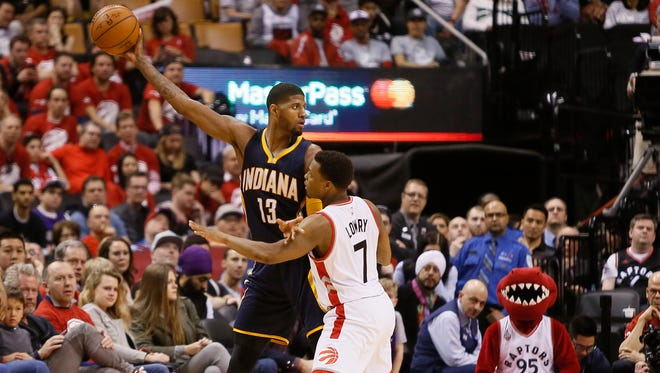 Indiana Pacers forward Paul George (13) plays keep-away with the ball as Toronto Raptors guard Kyle Lowry guards him during Game 1 of their playoff series Saturday, April 16, 2016,   at Air Canada Centre in Toronto. Indiana won 100-90.