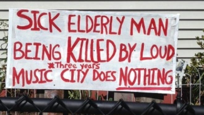 Dorothea Pelletier's sign in front of her Taunton home complaining about her neighbors' music listening habits and the effect it is having on her sick husband while the town does nothing to stop it.