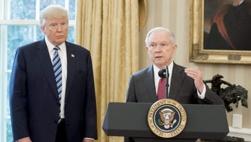 President Trump stands alongside Attorney General Jeff Sessions after Sessions was sworn in on Feb. 9, 2017, in the Oval Office.