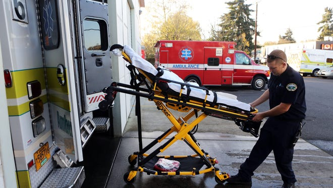 Robert Bade operates a powered stretcher at Rural Metro ambulances on Front Street NE.