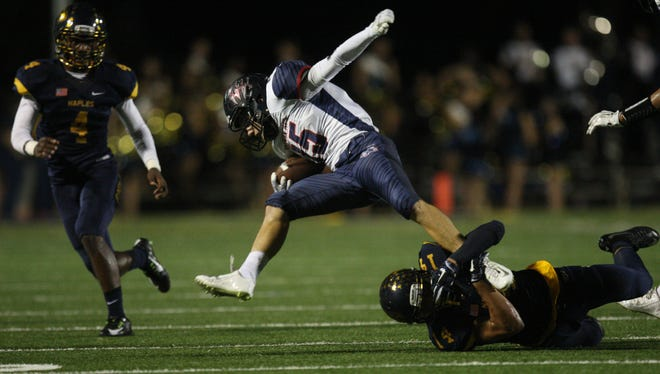 Action between Naples High School and Estero on Friday during the Class 6A regional quarterfinal playoff game at Naples High School. Naples beat Estero 58-0.