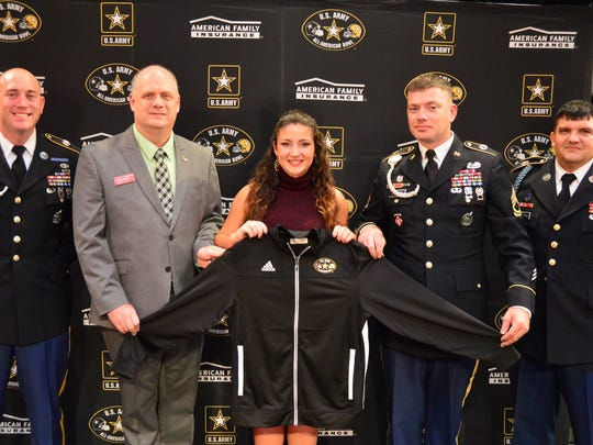 Arlington High School's Maria Kusior, center, receives her jacket as a member of the marching band for the U.S. Army All-American Bowl, on Sept. 30 at the school.