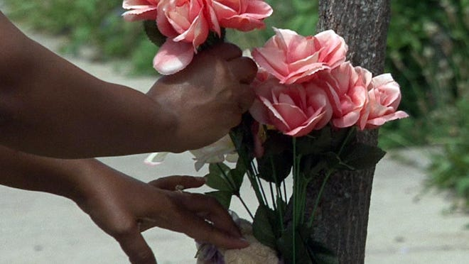 A flower is added to a memorial along Sewall Avenue in Asbury Park Wednesday, Jun 17, 2015, where an off-duty Neptune police officer shot and killed his former wife. ASBURYSHOOTINGFOLO0617C