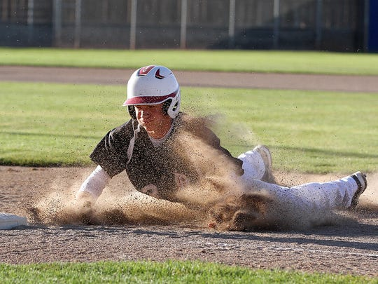 Dawson Marcum of the Demons slides back to first base during a game against the Halos on Thursday at Ricketts Park.
