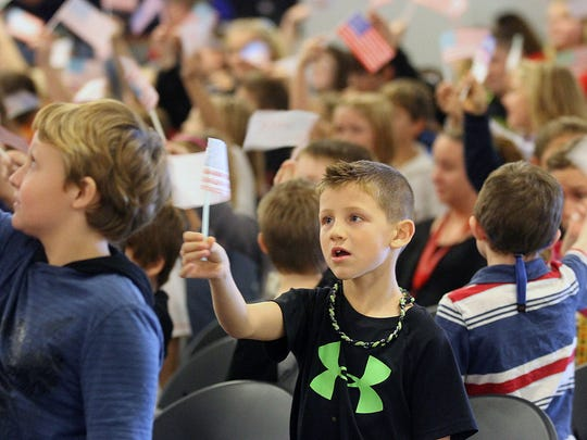 """Elgin Elementary School students wave handmade flags during the finale, """"This Is My Country,"""" at the annual Veterans Day concert Monday."""