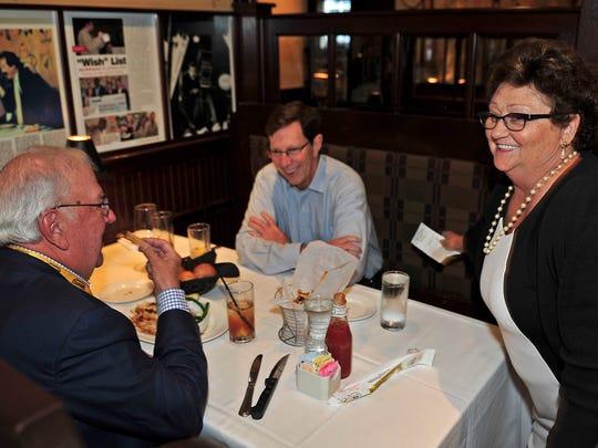 Rae Krenn, right, checks on customers Predators Chairman Tom Cigarran, left, and Predators general manager David Poile during lunchtime Thursday at The Palm restaurant in Nashville.