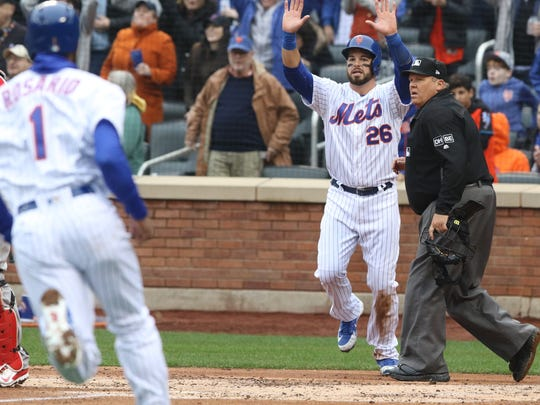 Amed Rosario comes home and is signaled to stay up by Kevin Plawecki as the Mets scored two runs in the second inning on a hit by Yoenis Cespedes.