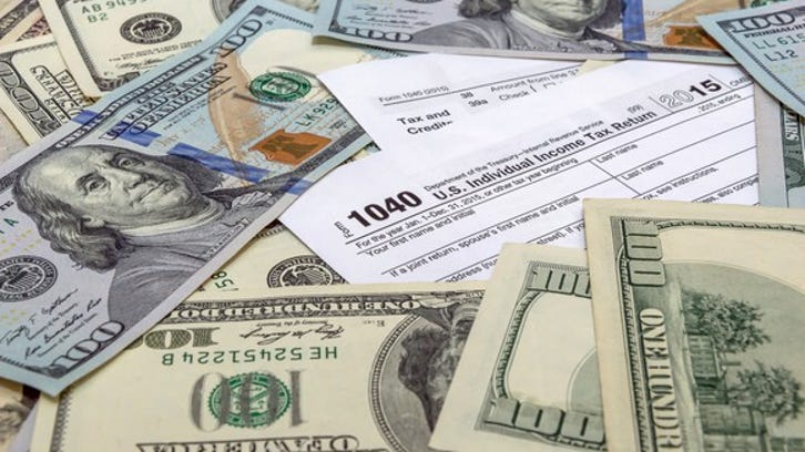IRS tax forms with money scattered on top.